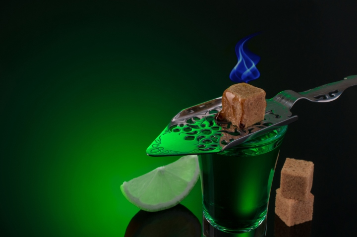 Absinthe shots with burning sugar and lime slices on dark background
